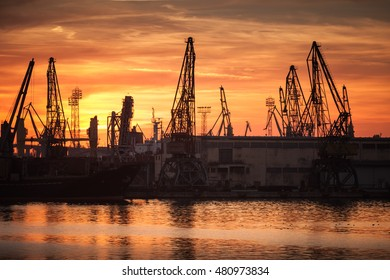 Silhouettes of cranes and industrial cargo ships in port of Varna at sunset