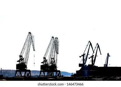 Silhouettes of cranes in the shipyard.