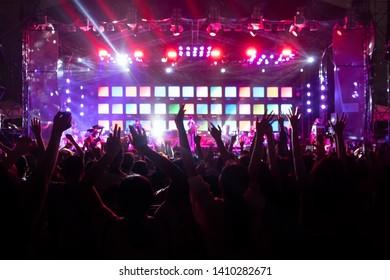 Silhouettes of crowd, group of people, cheering in live music concert in front of colorful stage lights.