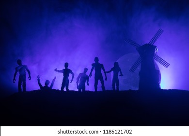 Silhouettes crowd of hungry zombies and old windmill on hill against dark foggy toned sky. Silhouettes of scary zombies walking at night. Horror Concept