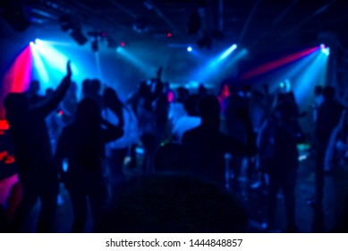 silhouettes of a crowd of people dancing in a nightclub on the dance floor at a party out of focus