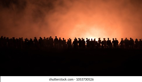 Silhouettes of a crowd standing at field behind the blurred foggy background. Selective focus. Revolution, people protest against government, man fighting for rights