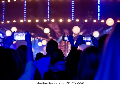 Silhouettes of crowds of spectators at a concert with smartphones in their hands.