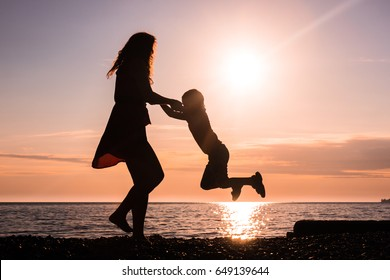 Silhouettes. Dance with the sun. Graceful girl dancing with her son.