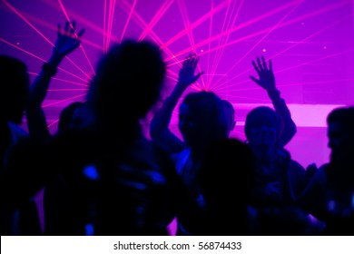Silhouettes of dancing people having a celebration in a disco club, the light show is sending laser beams through the backlit scene, FOCUS IN ON THE BEAMS!