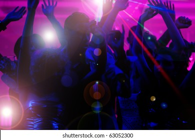 Silhouettes of dancing people having a celebration in a disco club, the light show is sending laser beams through the backlit scene - beware: very psychedelic forms and colors