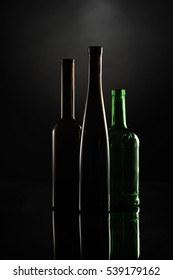 silhouettes of dark wine bottles on the black background contoured by the light