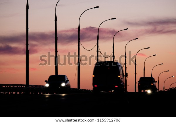 Silhouettes of defocused cars in front of street lamps and sunset sky