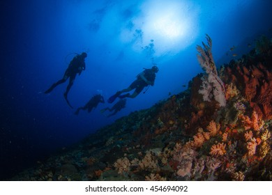 Silhouettes of divers swimming in the crystal blue water of Indonesia, Nusa Penida.