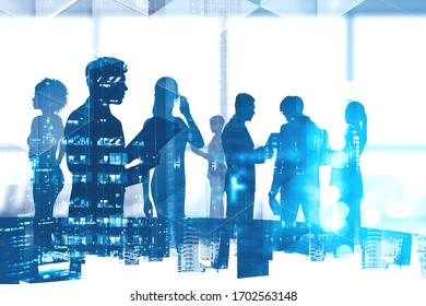 Silhouettes of diverse business people in blurry panoramic office meeting room with double exposure of night cityscape. Concept of communication and teamwork. Toned image