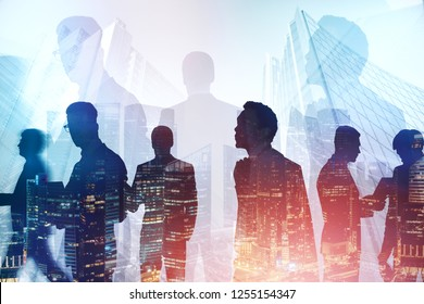 Silhouettes of diverse business team members working together over foggy cityscape background with double exposure of night city. Toned image double exposure
