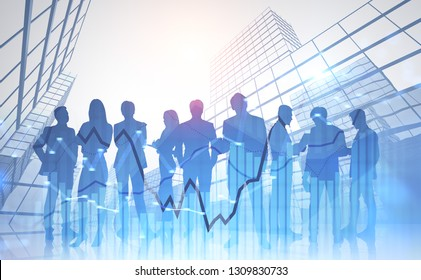 Silhouettes of diverse business team members working together over skyscraper background with double exposure of blue graphs. Toned image