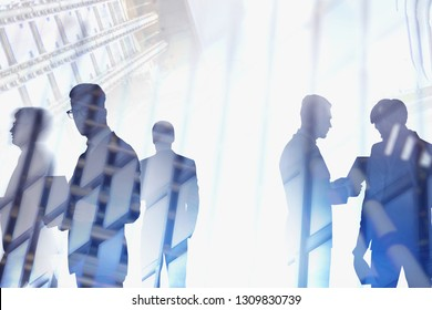 Silhouettes of diverse business team members working together and communicating over city sky and skyscraper background. Corporate lifestyle concept. Toned image double exposure