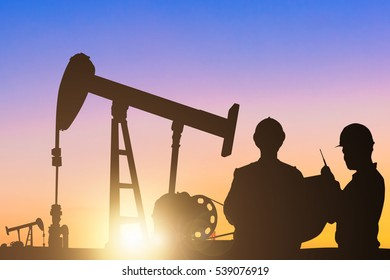 Silhouettes of Engineer and worker at oil rig pump of petrochemical industrial in sunrise sky