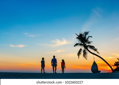 Silhouettes of family father with two kids at tropical beach during sunset