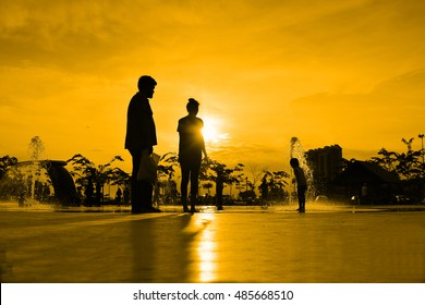 silhouettes of family playing in water fountain at sunset