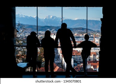 Silhouettes of family standing on castle and looking over old town Ljubljana to mountain range Kamnik–Savinja Alps in Slowenia, Europe