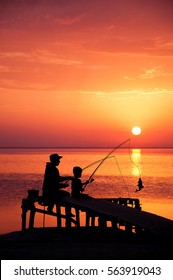Silhouettes of father and son, fishing from the pier in the ocean of surfing at sunset.