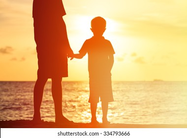 silhouettes of father and son holding hands at sunset sea