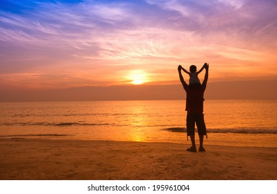 silhouettes of father and son on sunrise sea background,family concept