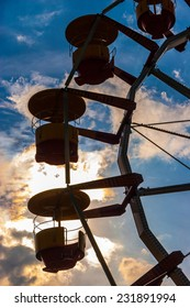 Silhouettes of ferris wheel cabins in amusement park at dusk.