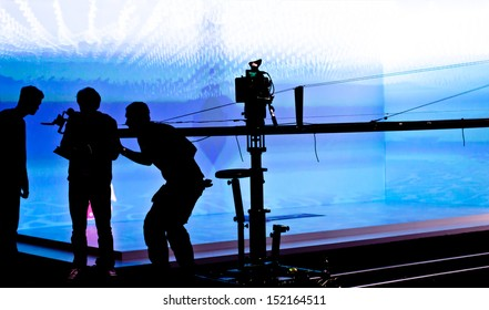 Silhouettes of film crew in front of  blue lighted stage. Selective focus.