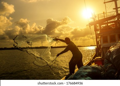 Silhouettes fisherman casting on a crab boat.