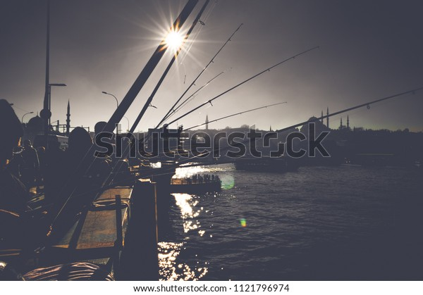 Silhouettes of fishermen fishing on Galata Bridge to relax and enjoy their hobby in Istanbul, Turkey