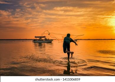 Silhouettes of the fishermen throwing fishing net during sunset in Dammam seaside Saudi Arabia