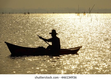 silhouettes fishermen working on little colorful boat in lake at sunrise time,select focus with shallow depth of field.