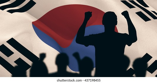 Silhouettes of football supporters against korea republic flag waving