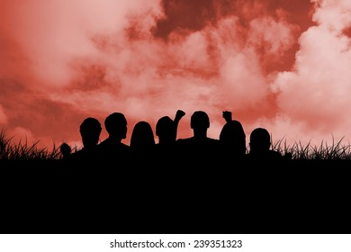 Silhouettes of football supporters against red sky over grass