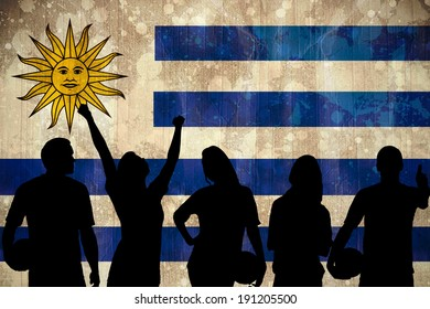 Silhouettes of football supporters against uruguay flag in grunge effect