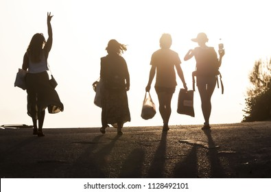 Silhouettes of four best friends walking in the sunset. One girl raises her hand. Four people silhouette against the sundown as they walk and converse. Set for the picnic. Three girls and one boy.