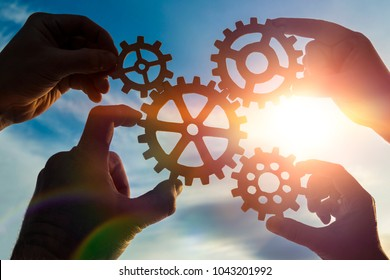 Silhouettes four hands collect the gear from the gears of the details of the puzzles. against the background of sunlight. Concept business idea. Teamwork. strategy, cooperation. Close-up