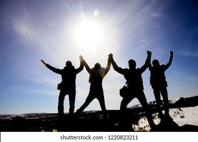 Silhouettes of four people standing together holding hands up against sunny sky in the mountains. winter time season. sun rays.