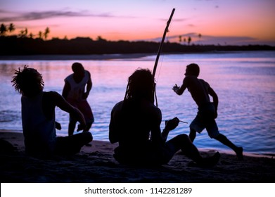 Silhouettes of four unrecognizable capoeiristas sat on the beach paying berimbau and drum instruments while watching two dance during sunset in Bahia, Brazil.