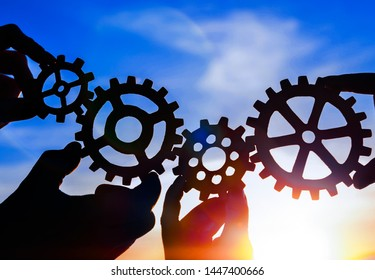 Silhouettes of gears in the hands of people against the evening sky.  Interaction, teamwork.