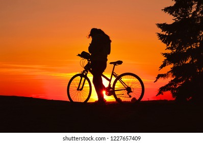 silhouettes of girl with bycicle on the Kalemegdan park hill with warm colorful  orange sunset in background. Belgrade Serbia