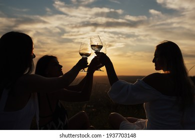 Silhouettes of girls holding glasses of wine making a toast at the nature picnic on summer sunset.