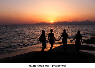 silhouettes of girls holding hands at the beach showing their friendship