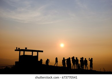 Silhouettes of a group of people on the mountain at sunset