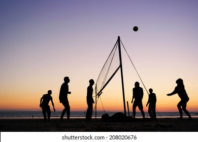 Silhouettes of a group of young people playing beach volleyball on the beach in Brittany, France