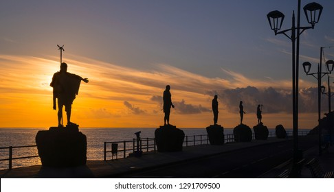 Silhouettes of guanche chiefs against the background of the dawn rising above the ocean. Candelaria promenade - Tenerife Island.