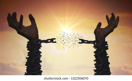 Silhouettes of hands are breaking chain. Freedom concept.