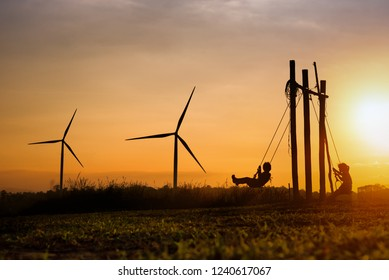 Silhouettes of happiness life of child to playing swing in turbine wind park renewable on sunset. Family Responsibility, Corporate Social Responsibility and sustainable energy concept.