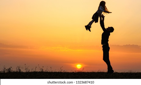 Silhouettes of happy child rushes into hands of father.