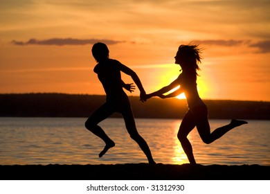 Silhouettes of happy couple having fun on seashore at sunset