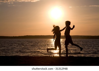 Silhouettes of happy couple having fun and laughing during summer vacations
