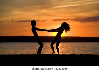 Silhouettes of happy couple holding each other by hands at sunset